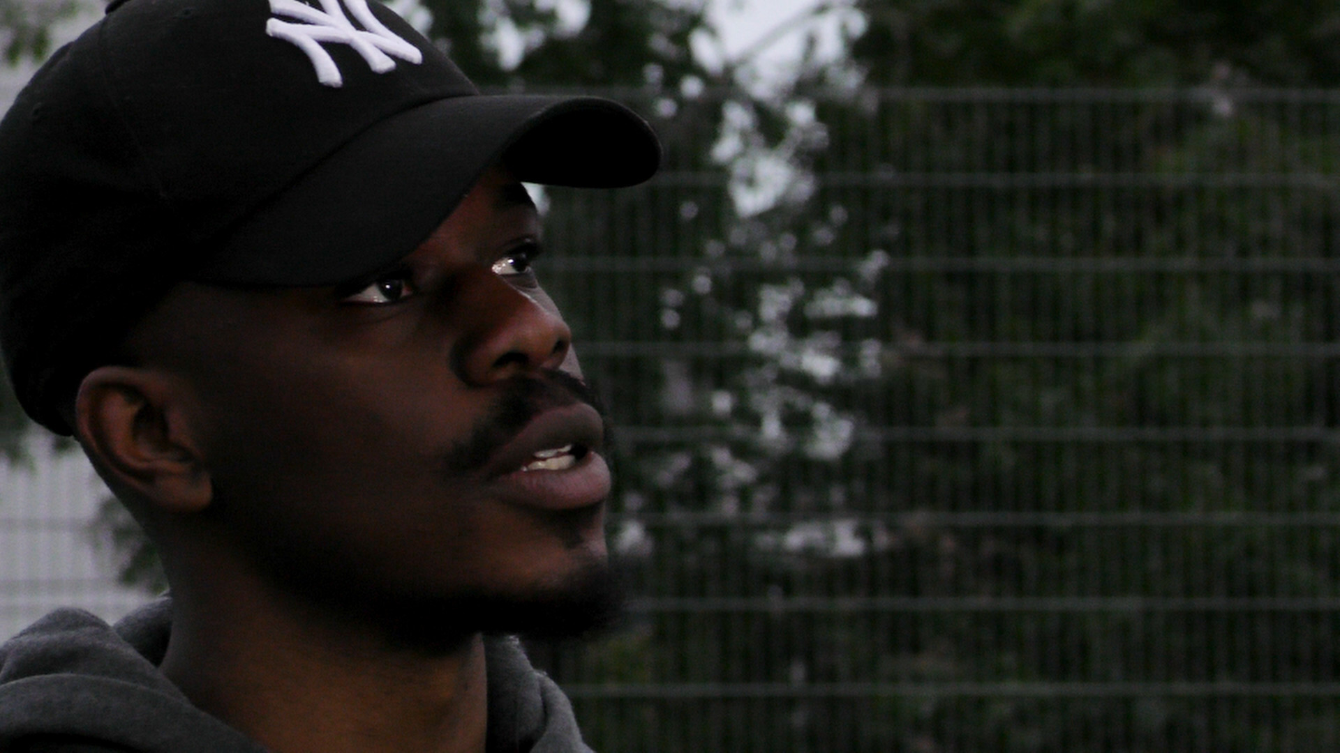 Still from Life Now, Movement Films Music Video of a close up of Jepeto Knockz looking off in the distance on a basketball court