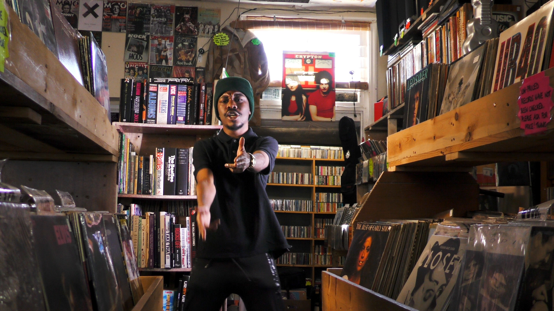 Still from Life Now Music Video of Jepeto Knockz rapping towards camera in a Vinyl Record Store on Movement Films Shoot