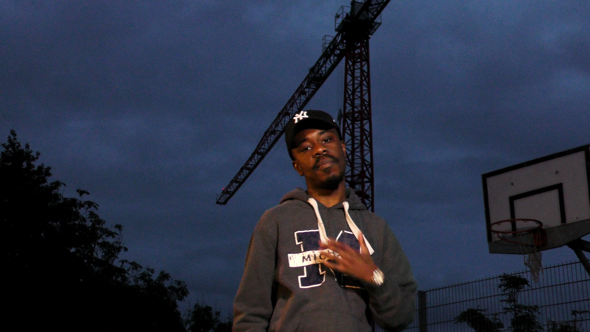 Still from Life Now music video of Jepeto Knockz rapping towards the camera at night on a basketball court
