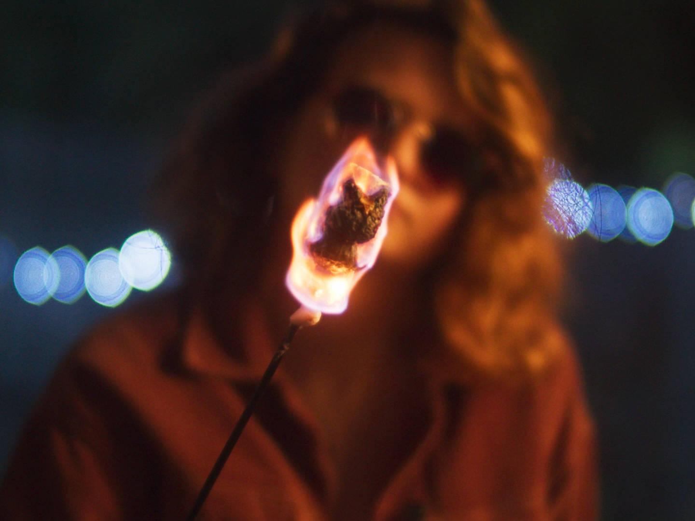 Still from summer film, shot of marshmallow burning